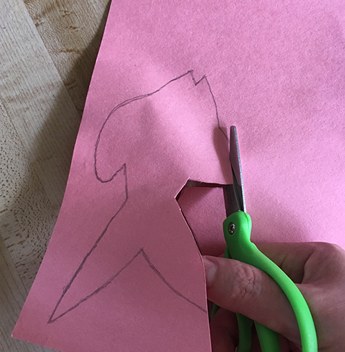 Cutting out the outline of a fish drawn on pink paper