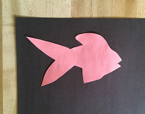 Pink fish shape placed on black construction paper