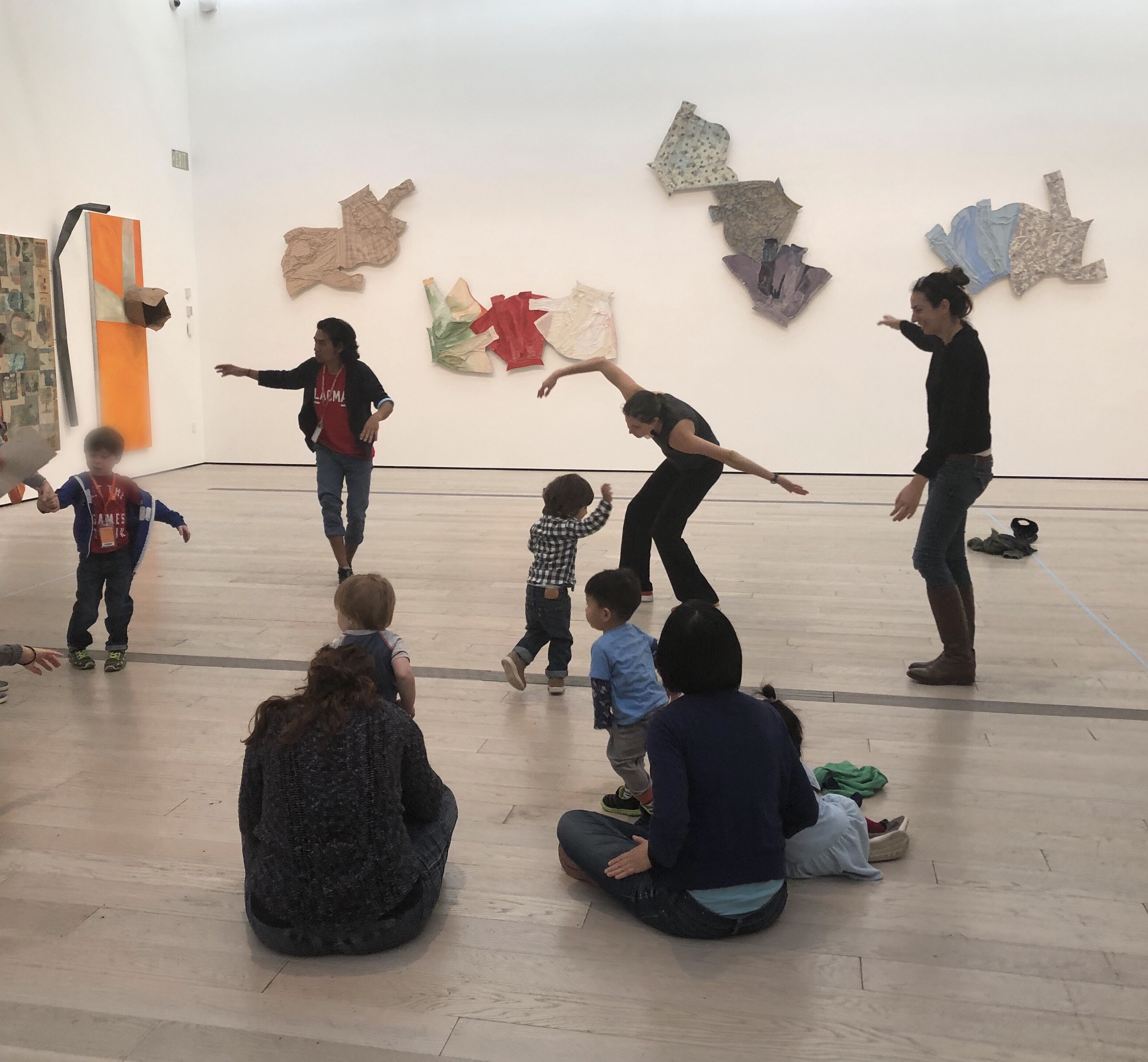 Andell Family Sundays participants dancing in front of Robert Rauschenberg's The 1/4 Mile or 2 Furlong Piece.