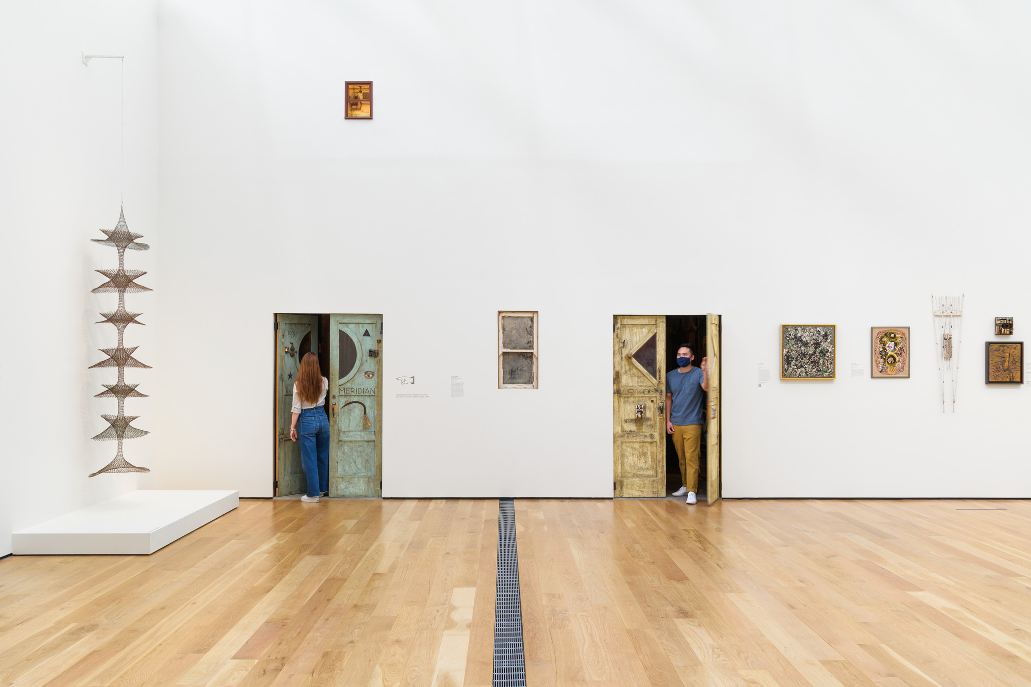 """Gallery view of LACMA's Modern Art installation, with visitors emerging from the doors leading to Michael C. McMillen's """"Central Meridian"""""""