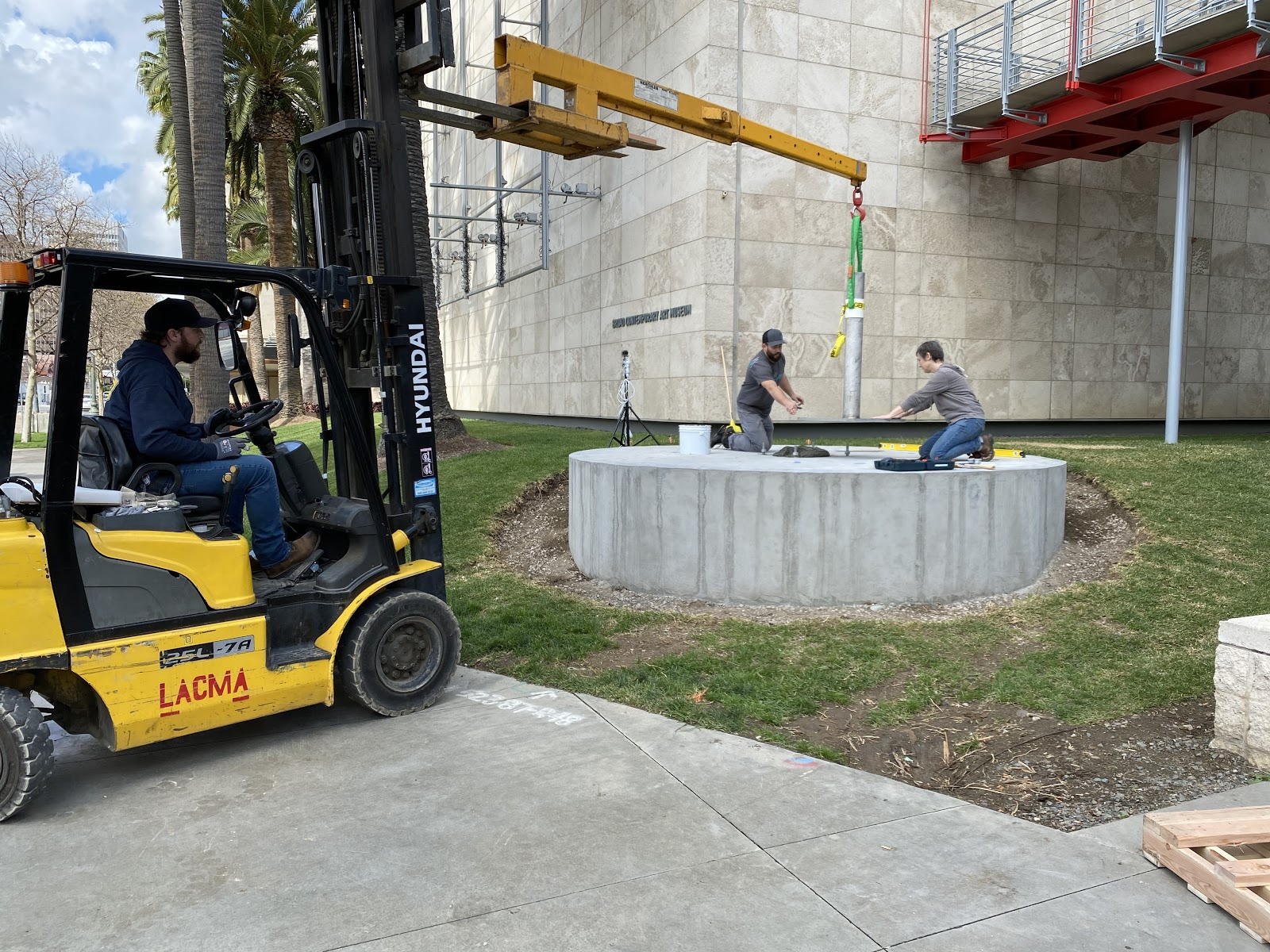 The day before the sculpture arrived, we installed its mount onto the concrete pedestal. We worked closely with Manager of Gallery Construction Jeff Young, to embed anchor bolts in the exact locations needed in the concrete pad as it was poured. From left to right Jordan Mesavage, Luke Boehnke, and Julia Latané. Photo by Elspeth Patient