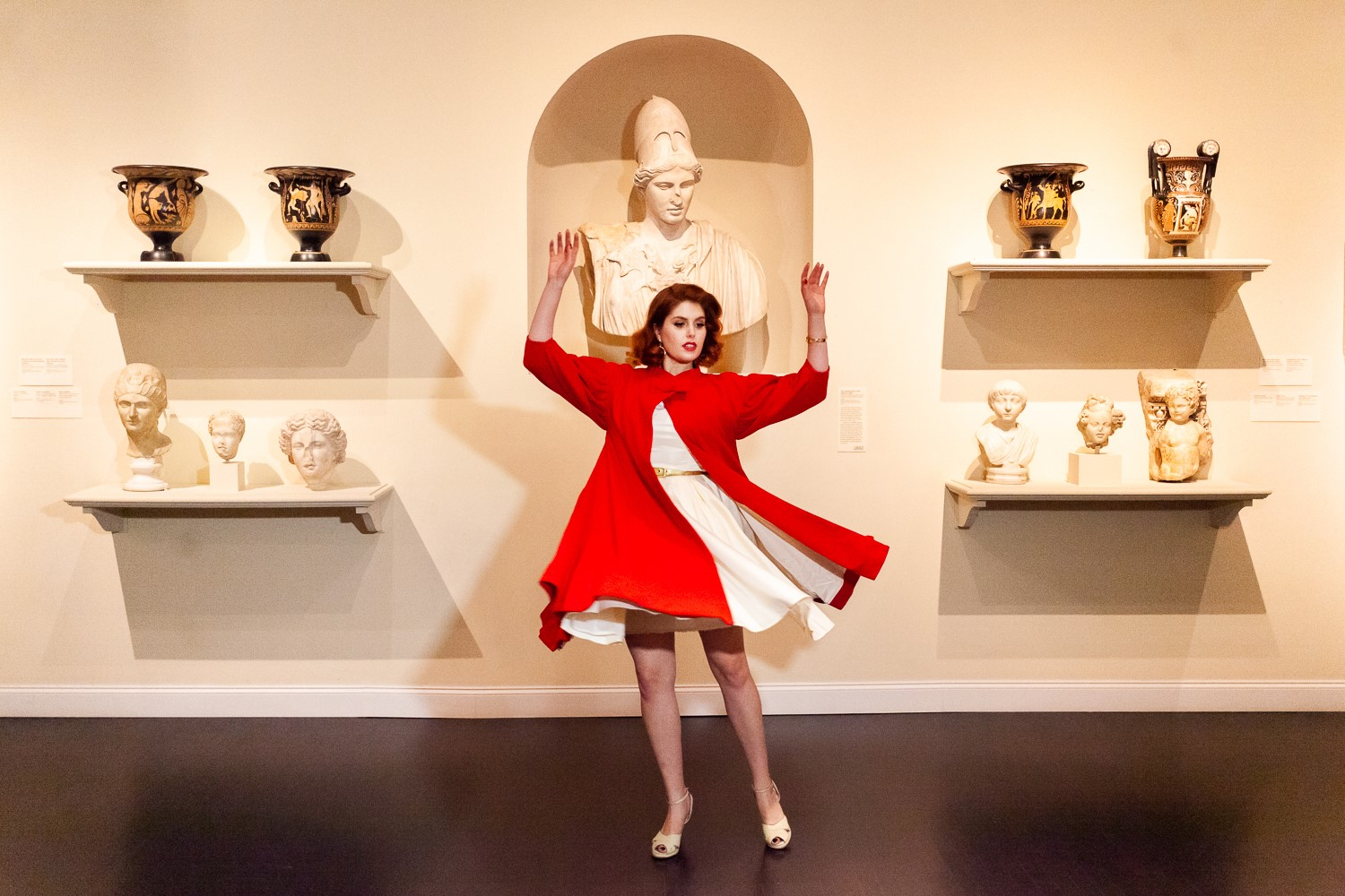 Woman in white dress and red coat twirls in front of sculptures