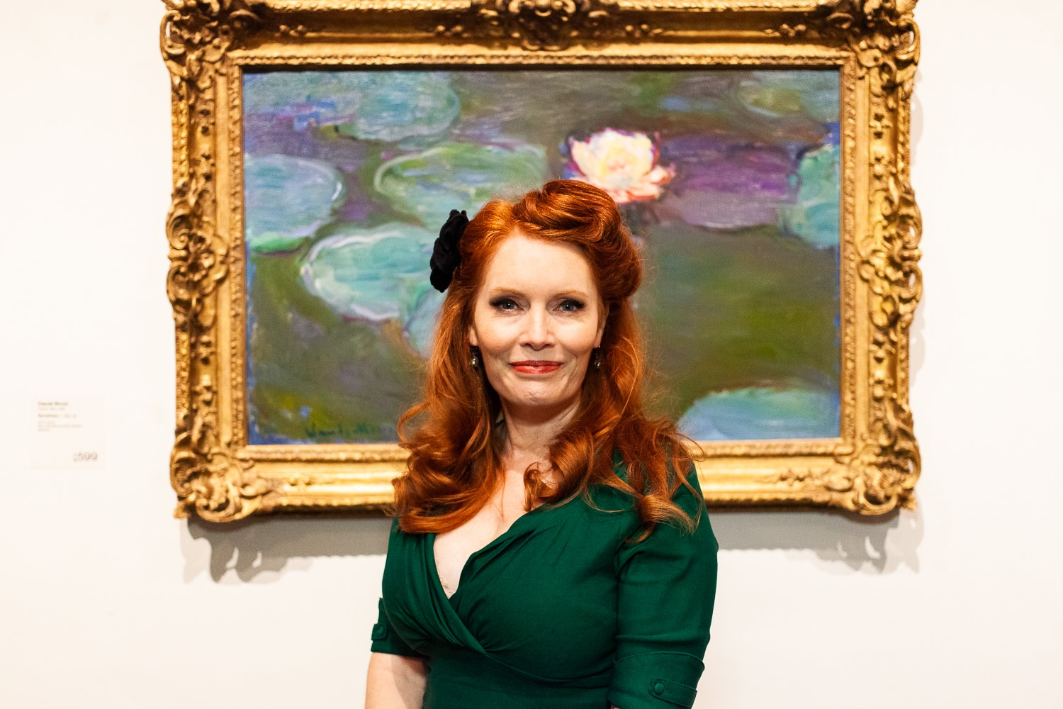 Woman standing in front of painting in a green dress with black flower in her hair