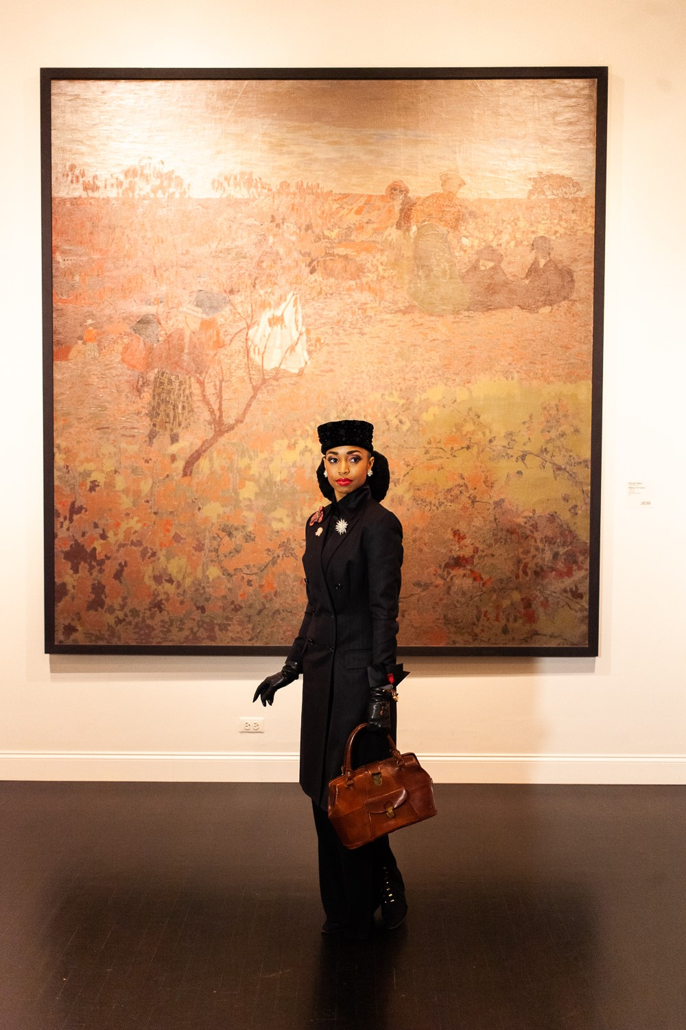 Woman dressed in all black standing in front of large painting