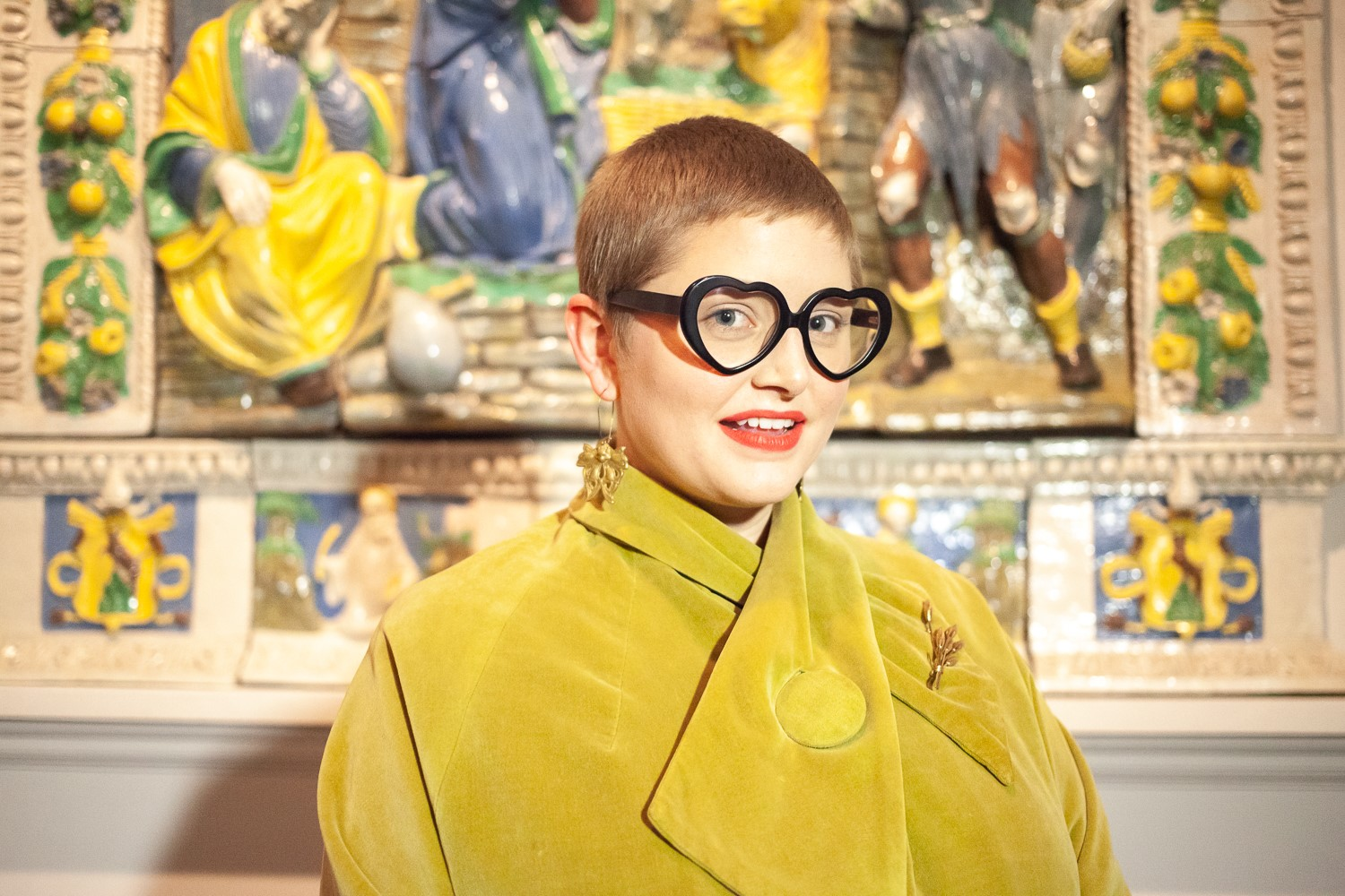 Woman in yellow coat and black heart-shaped glasses standing in front of artwork