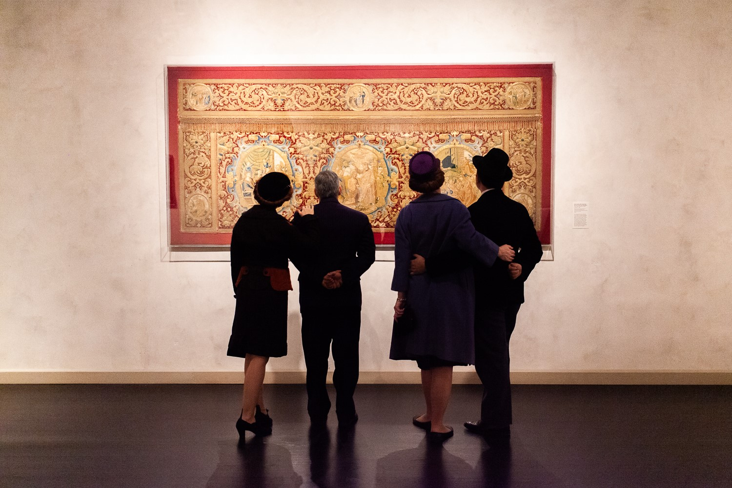 Four people standing looking at large painting in gallery