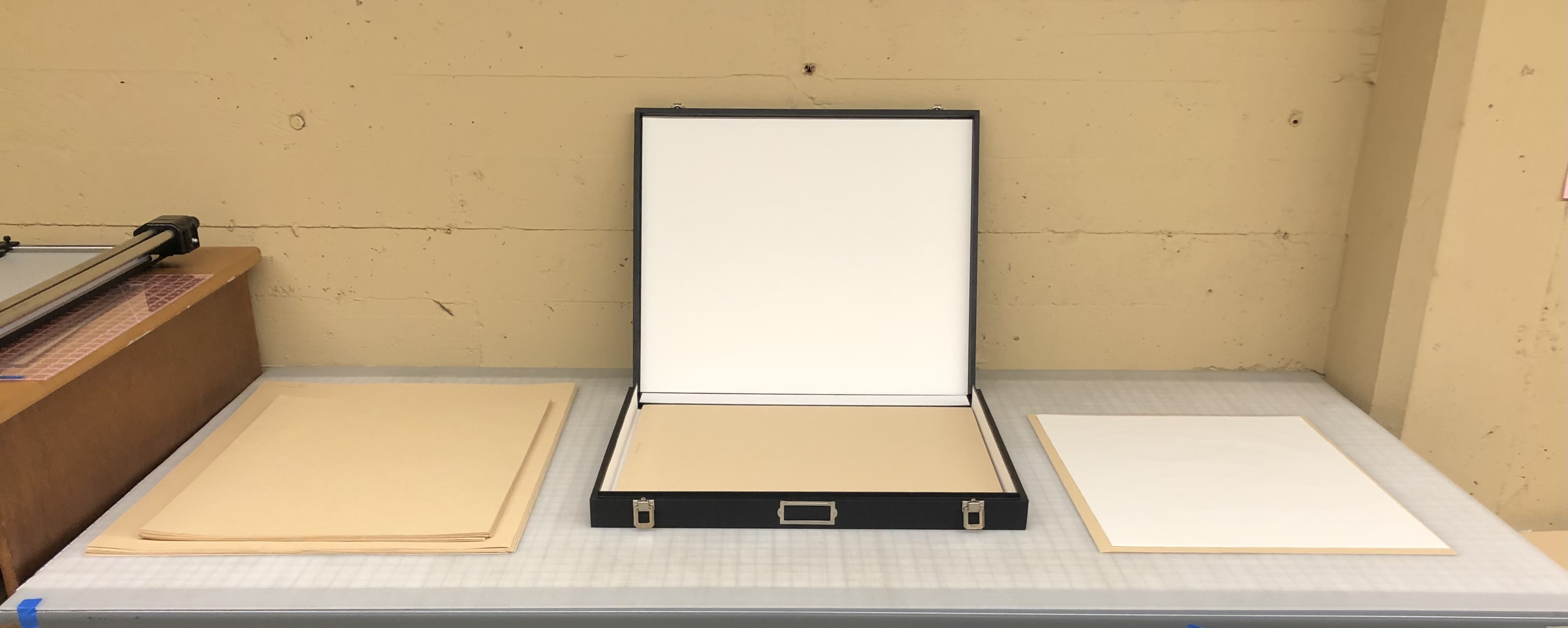 Materials used to rehouse photographs. From left to right: buffered folders, a box, and Photo-Tex, photo courtesy of Bella Quijano