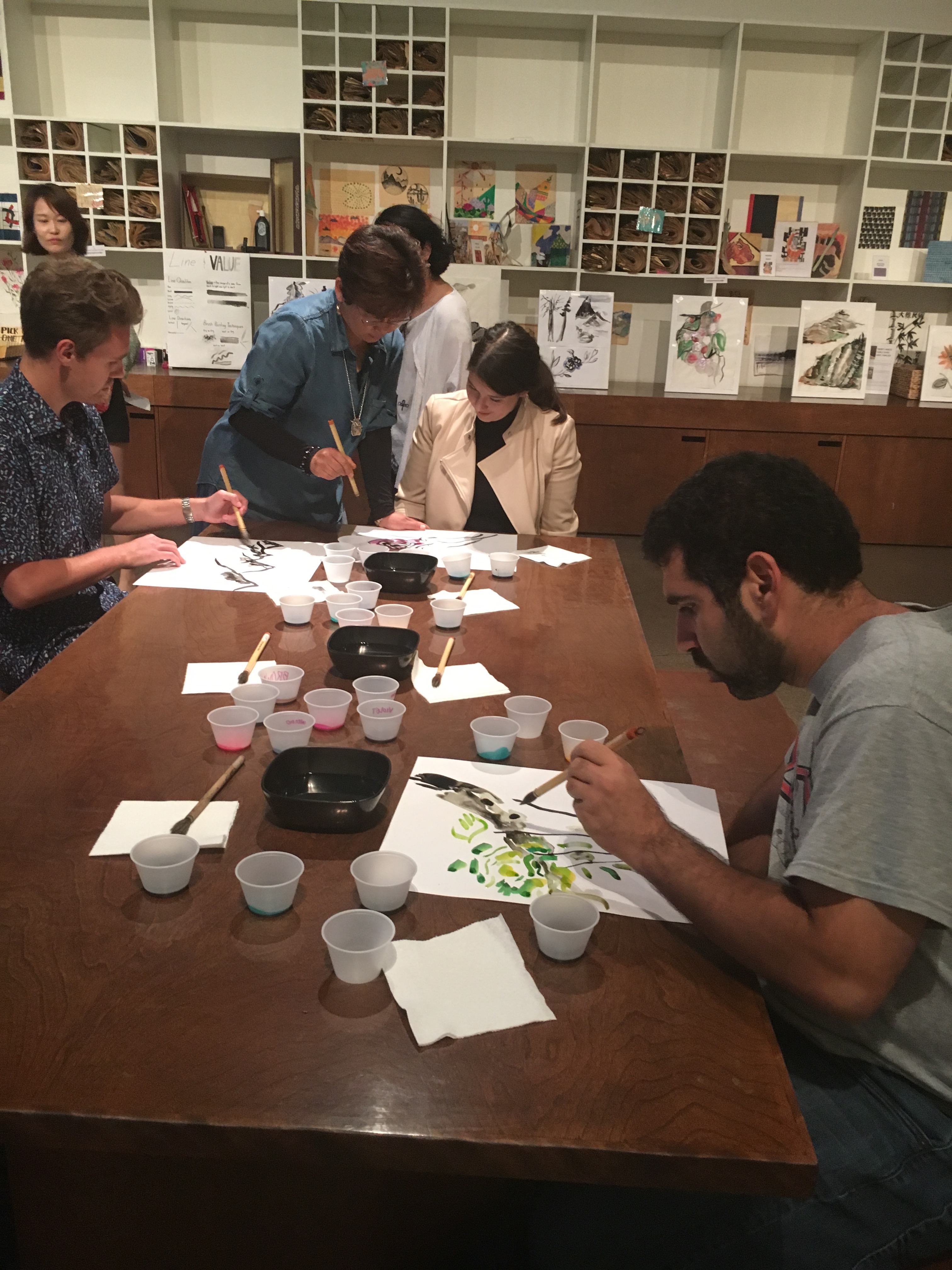 Artist Kyungsoo Lee instructs a group of participants in the techniques of Korean brush painting.