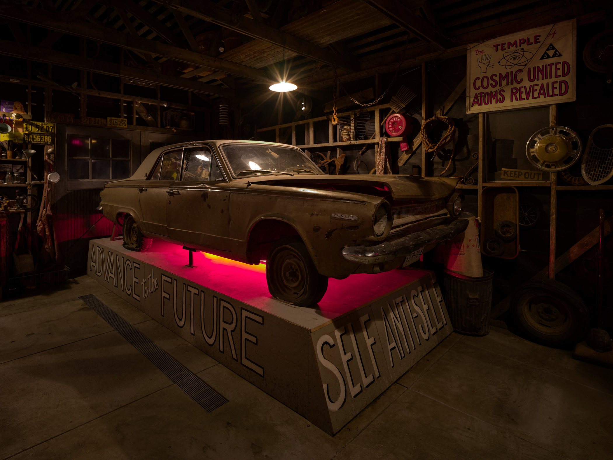 """View of Michael C. McMillen's """"Central Meridian,"""" a darkened garage installation with vintage car"""