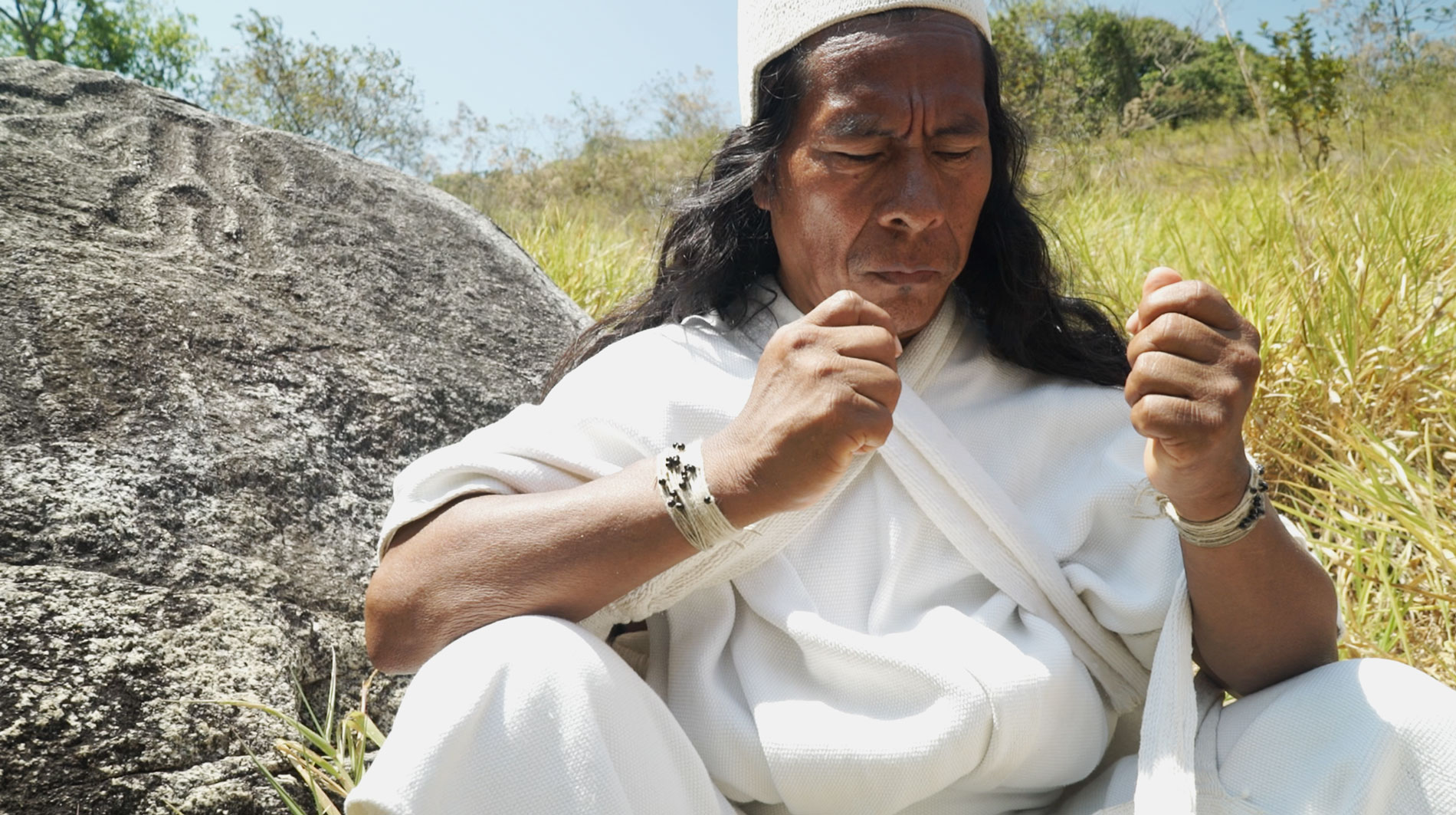 Mamo Camilo meditates over cotton strands before making the offering