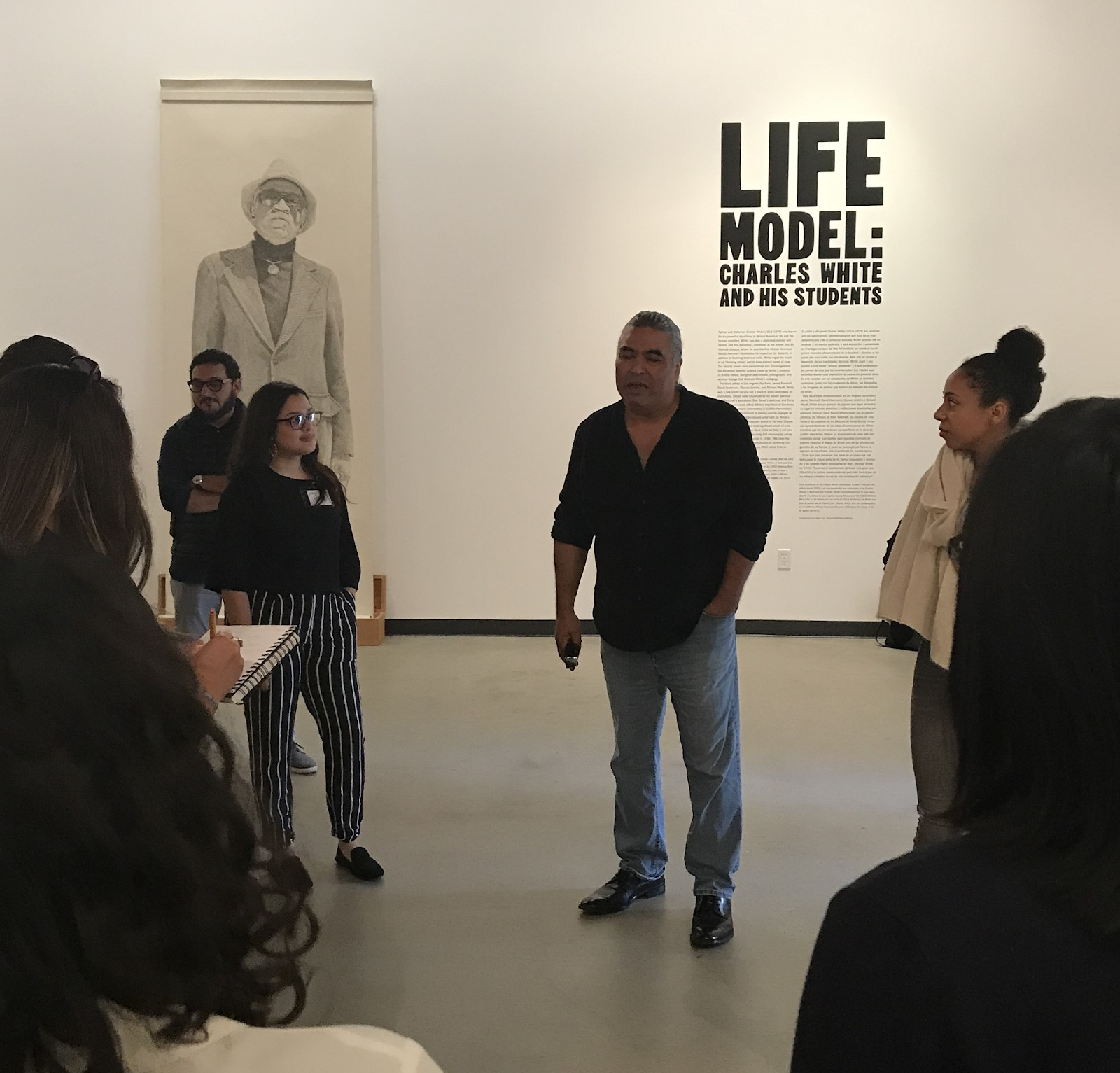 Ian White discussing Life Model: Charles White and His Students with the 2019 Mellon Summer Academy students at the Charles White Elementary School gallery, © Kent Twitchell, photo courtesy Hilary Walter