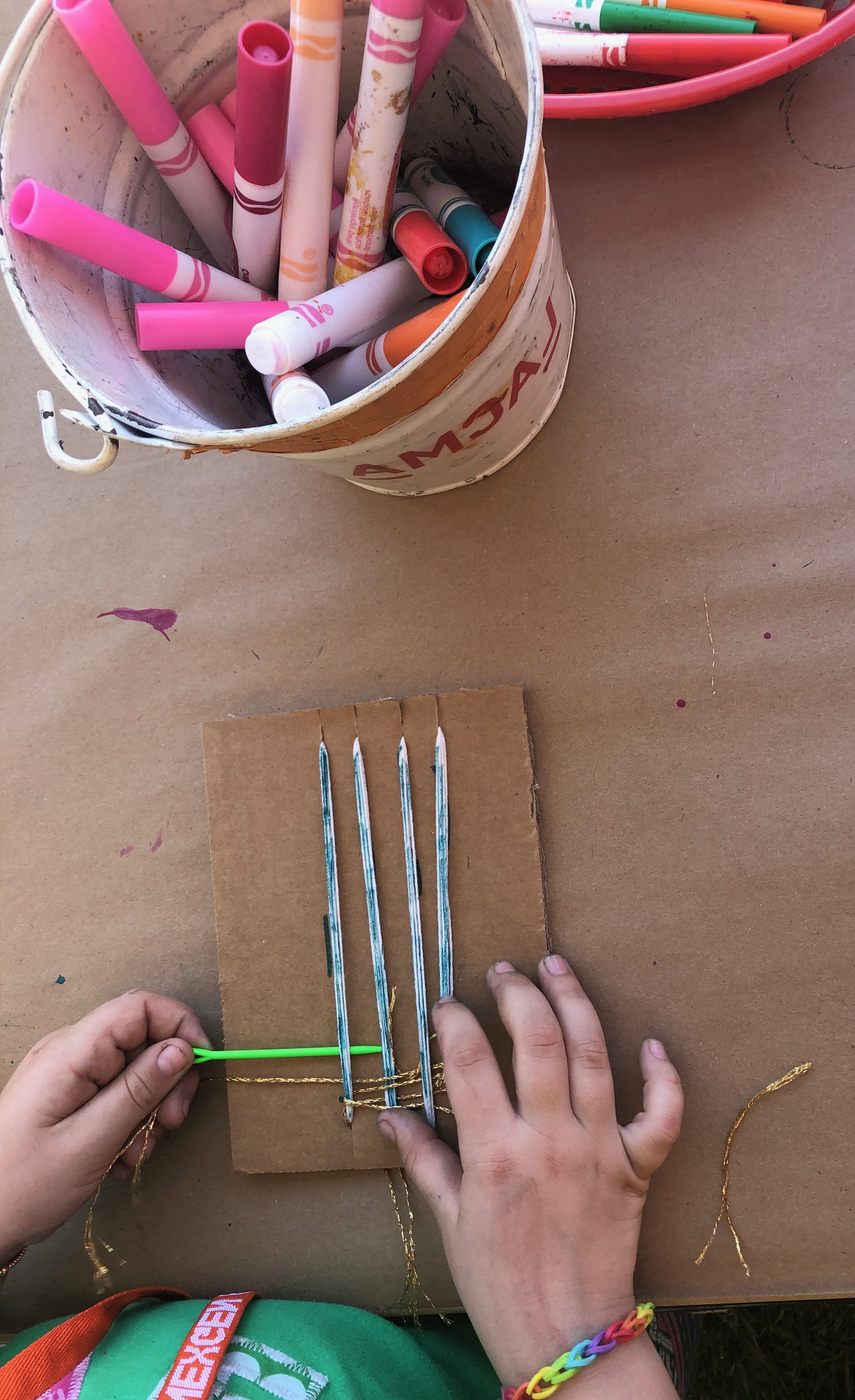 Child creating a weaving project in artist Julianna Ostrovsky's workshop