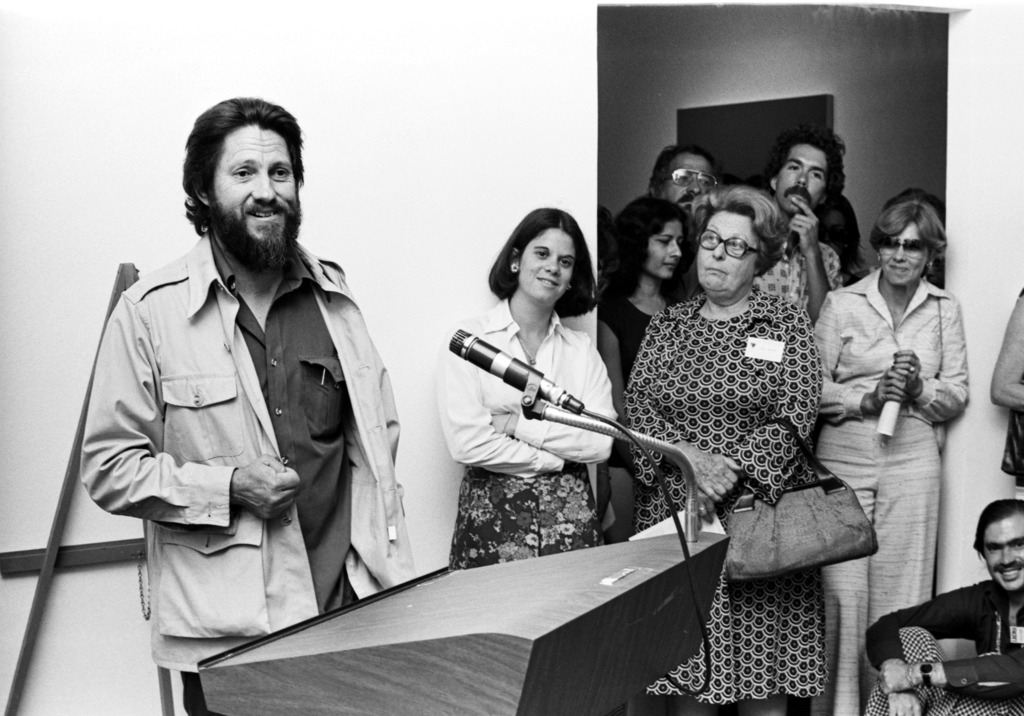 Artist Ed Moses (left), with curators Stephanie Barron (center) and Maurice Tuchman (not pictured), speaking with visitors at LACMA in 1976 on the occasion of the exhibition Ed Moses: New Paintings, photo © Museum Associates/LACMA