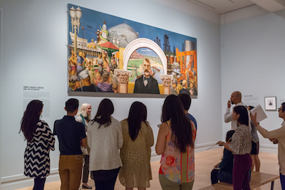 The Andrew W. Mellon Summer Academy participants viewing Edward Biberman's Abbot Kinney and the Story of Venice, lent by the United States Postal Service ®. Recent conservation provided by Joel Silver. Photo © Museum Associates/ LACMA