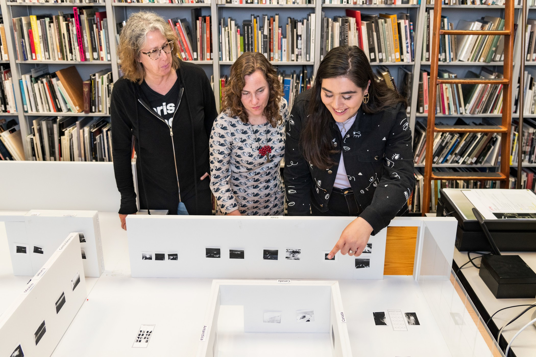 From left: Eve Schillo, Rebecca Morse, and Danielle Pesqueira with a Thomas Joshua Cooper: The World's Edge exhibition model
