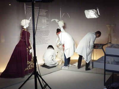 LACMA and Les Arts Décoratifs staff installs a vitrine that displays late 19th century garments