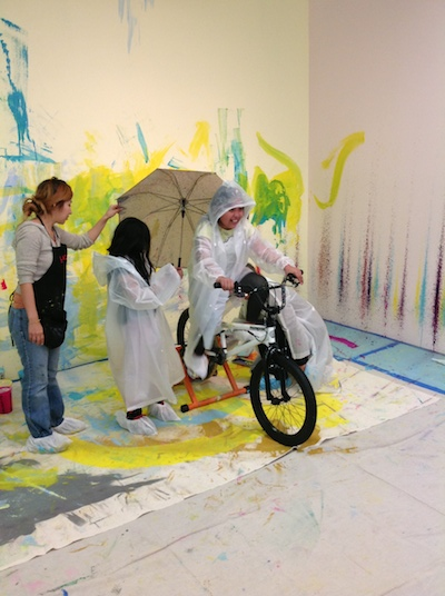 Students operate a stationary bicycle to create paint splatters on the wall.