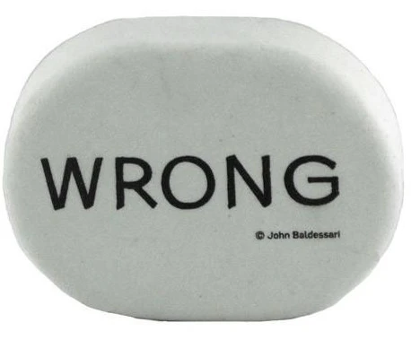 "large, white, oval-shaped eraser with the word ""WRONG"" in bold, black, block letters across it"