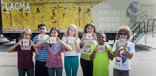 Students show their art projects while standing in front of the Ancient World Mobile.