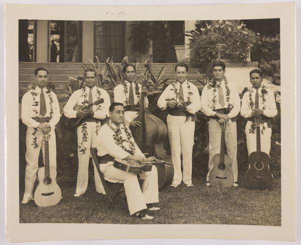 sepia toned image of a band standing outside a hotel—six men are standing, one is sitting in a chair in front of the group, all are wearing collared shirts, ties, dress pants