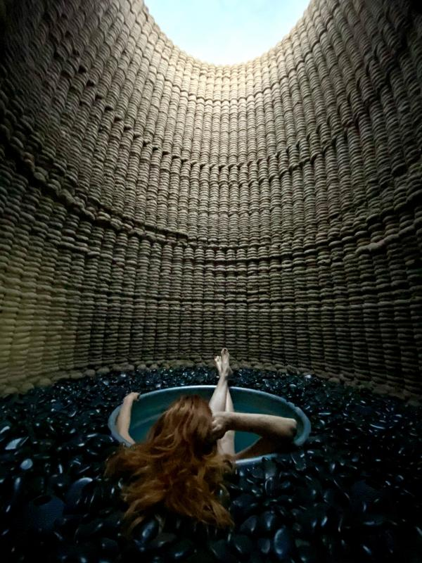 woman with red hair sitting in round tub that is submerged in black rocks inside a cylindrical-shaped structure, a circle of blue sky visible at top through opening in structure
