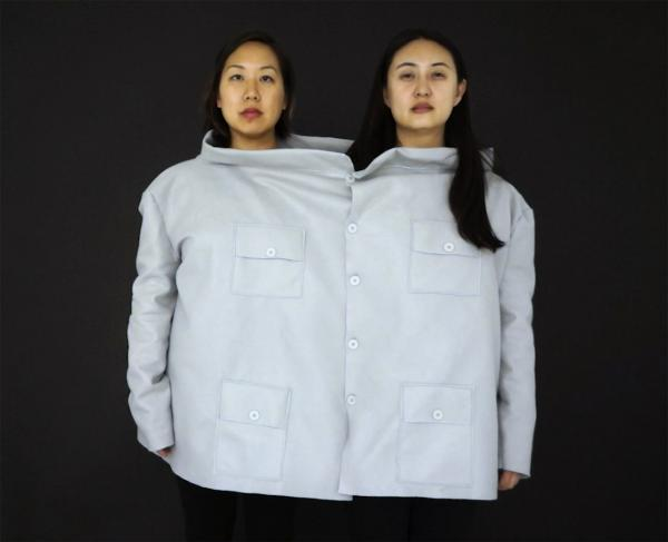 image of two women in a large shirt against a black background