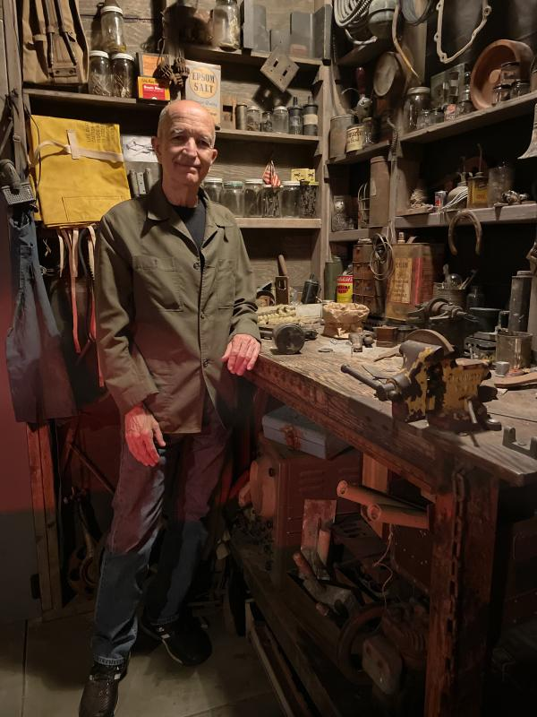 """Michael C. McMillen standing at a darkened work table in his installation """"Central Meridian"""""""