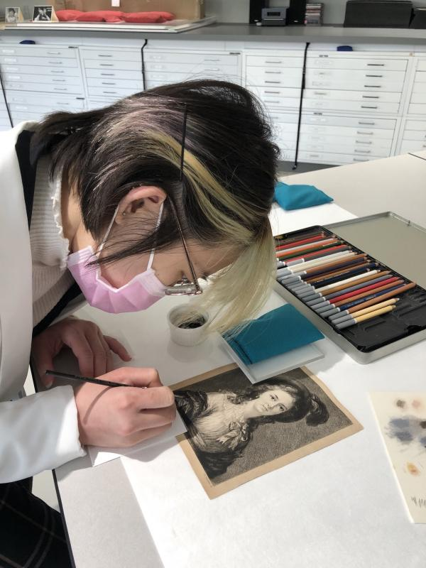 Conservation intern painting a black and white print of a woman