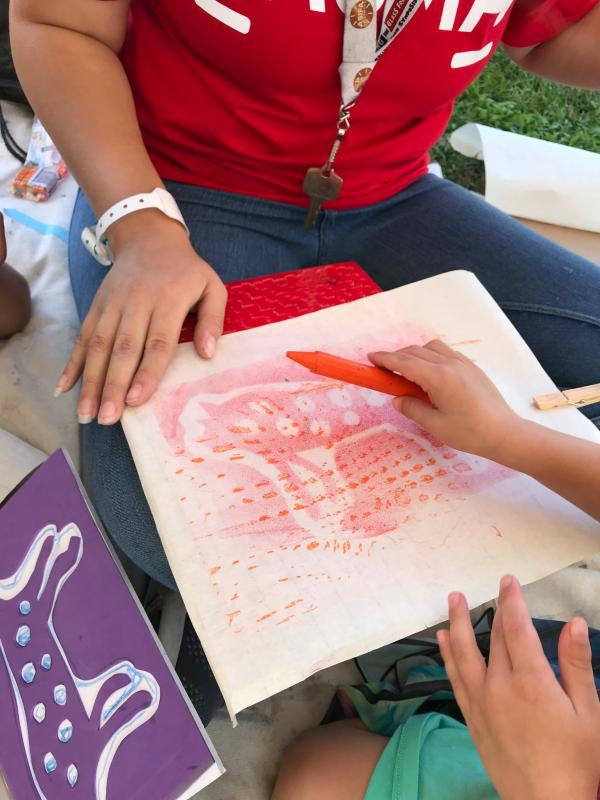 Toddler working on a pictograph rubbing in artist Eszter Delgado's workshop