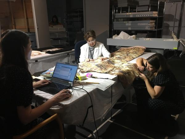 Costume and Textiles staff at work: Sharon Takeda (center) is verbally cataloging the kimono while Jennifer Iacovelli (left) enters the information into the database, and Michaela Hansen (right) is assessing the weave structure.