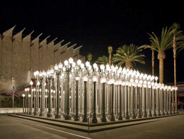 nighttime picture of Chris Burden's Urban Light illuminated at LACMA, an outdoor sculpture comprising 202 restored cast iron antique street lamps
