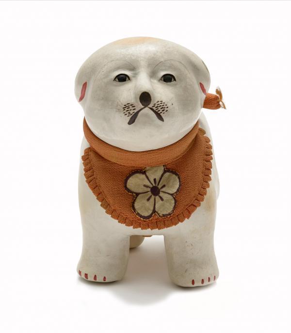 small white dog wearing an orange bib