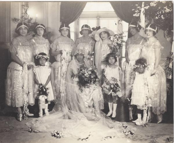 A group of women and three young girls in wedding finery and headpieces pose for a portrait
