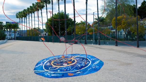 Blue portal on ground with red yarn emerging into the air with palm trees in background