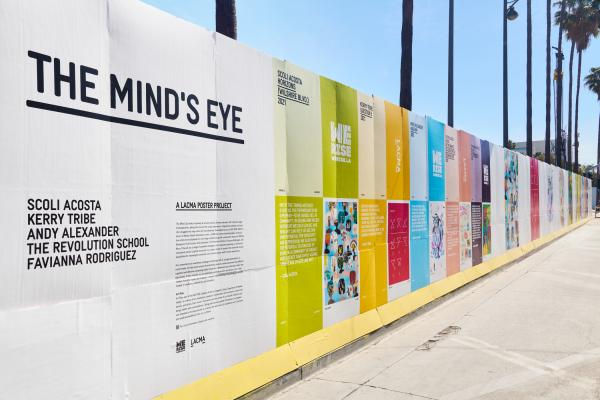 Colorful posters line a construction wall