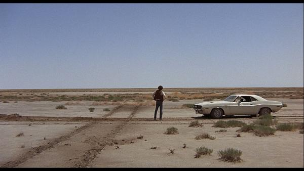 Man standing next to old car on desert road