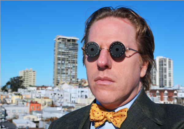 Jonathon Keats modeling a pair of sunglasses of his design whose lenses  dilate in time with his breathing cec5966436