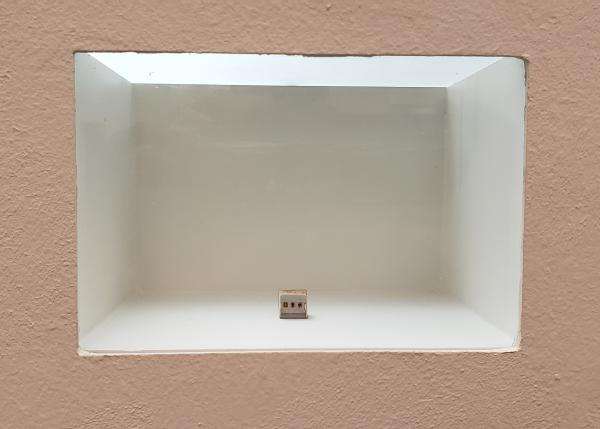 A tiny gallery of oil paintings displayed in a wall vitrine