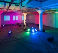 Diana Thater's installation Yes, there will be singing—an image of an open, warehouse-type interior with colored lights illuminating the room