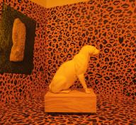installation of room with orange and black leopard print walls and floor with a white leopard statue in the center