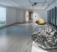 Installation photograph, featuring Zhan Wang's Beyond 12 Nautical Miles Floating Rock Drifts on the Open Sea (2000) and Gold Mountain (2007), in the exhibition The Allure of Matter: Material Art from China