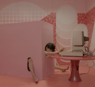 Woman's head and limbs emerge from a pink box to type on a computer in a surreal video still