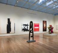 Gallery view with sculptures and paintings