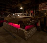Installation of Michael C. McMillen's Central Meridian, a dark, workshop-like space featuring a vintage car