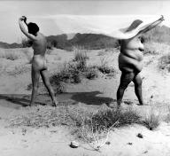 black and white image of two nude women standing apart, facing away from each other in the desert, a sheer piece of fabric stretched out between them, held over their heads