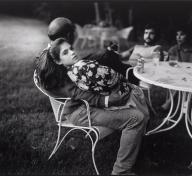 Black and white photo of man on lawn chair with girl on his lap