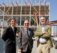 Three men stand in front of a three story building under construction