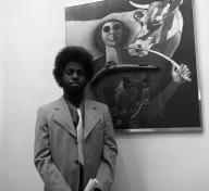 Black and white photo of Timothy Washington in front of painting