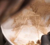 Close-up of gold dust being brushed onto the filled-in cracks of a white bowl