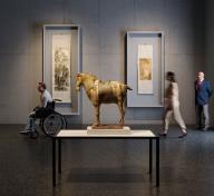 Sculpture of horse in the middle of a dark art gallery with visitors